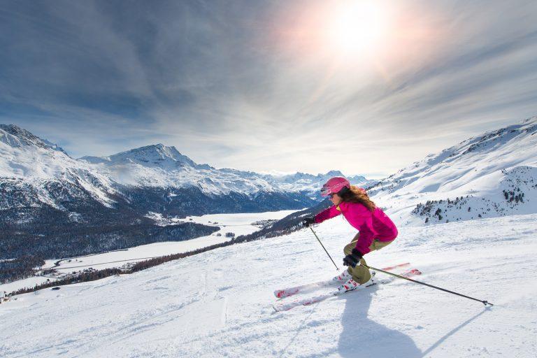 Skieuse en descente au soleil